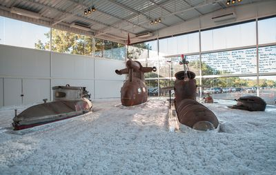 installation view of a large room with a white floor mimicking a seascape and foam, while the top halves of three large submarines and two smaller ones lay on the ground, half submersed in the illusion