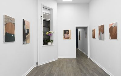 installation view of white walls leading back to a doorway with three paintings hung on either side of the room and a windowsill with flowers on it