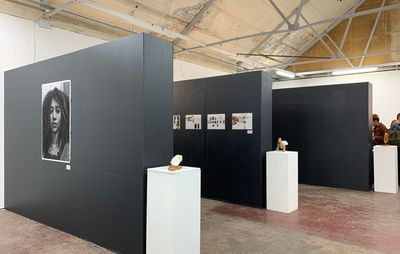 installation view of three grey freestanding walls with artwork hung on them and three white plinths with small sculptures on them