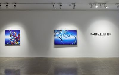 installation view of exhibition title on a white wall next to two blue paintings