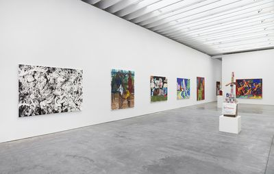 installation view of large exhibition space with a selection of paintings by various artists hung on the walls