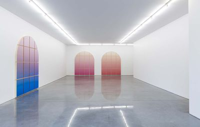 installation view of three different coloured window shapes set against white walls