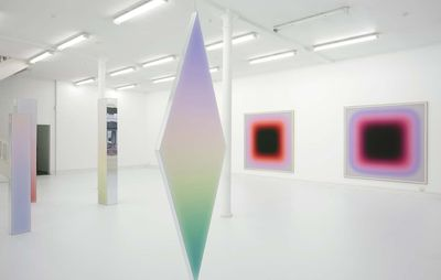 installation view of square paintings on the walls and a large diamond shape hanging from the ceiling