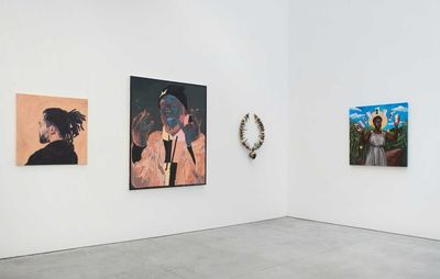 installation view of three paintings and a small sculpture hung on two white walls