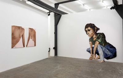 a pair of paintings of nude male and female torso's hang centrally on a white wall of an exhibition space with a larger mixed media installation of a woman crouching on the adjacent wall