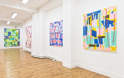 installation view of four large patterned abstract paintings of differing colours hung on white walls