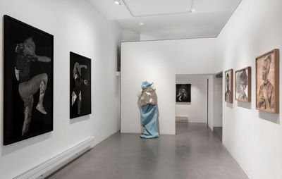 installation view of numerous white walls where paintings hang and a life-size sculpture stands