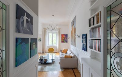 installation view of domestic interior with paintings spread out on walls above and around furniture and windows
