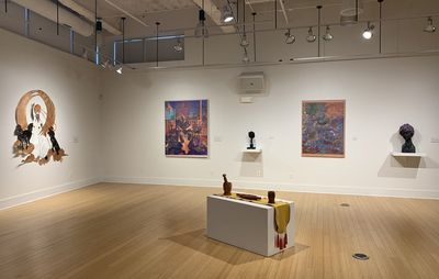 installation view of two paintings interspersed with sculptures on a white wall