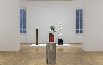 installation view of central wooden plinth with a small sculpture on and two sculptures on pedestals of varying heights behind them