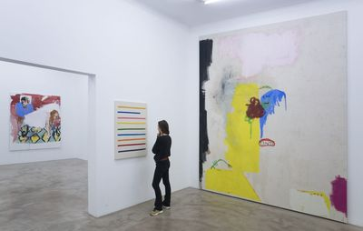 installation view of a woman looking at a small painting hung on a white wall, with a very large abstract painting to her right