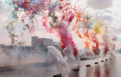 explosions of red, orange, blue and yellow paints erupting from a line of fireworks spread across a rooftop