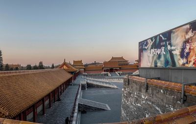 panoramic view of rooftops and a vast sky above it, with a billboard on the right of the photograph with a colourful abstract advertisement for Cai Guo Qiang's solo exhibition in Beijing