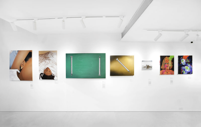 installation view of a white-walled gallery space with seven paintings hung and horizontally aligned across the wall