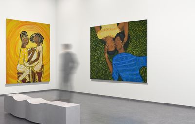 installation view of two large paintings, each of two women, hung on white walls
