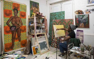 artist seated in studio surrounded by paintings and tools