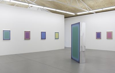 installation view of an exhibition space with six paintings of various colours hung on the walls, with a rectangular free-standing installation placed centrally in the room