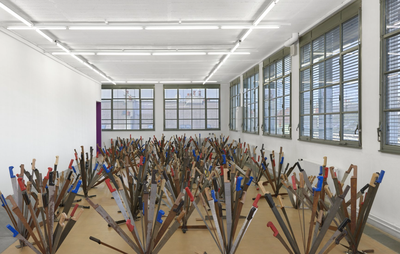 installation view of room filled with flowers made from swords