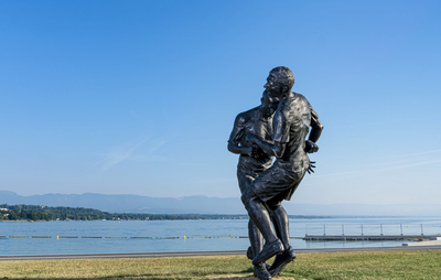 large sculpture placed outdoors of two footballers entangled