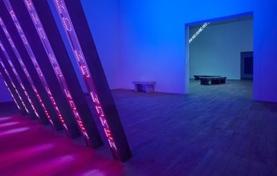 installation view of an exhibition room illuminated with purple and blue lights