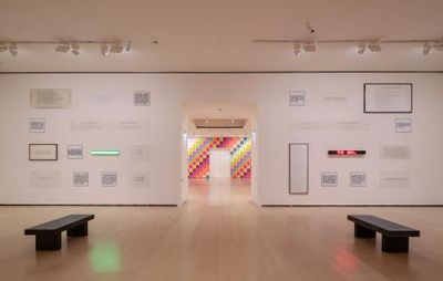 installation view of a white wall with a doorway in the middle, flanked by roughly two dozen framed texts on either side
