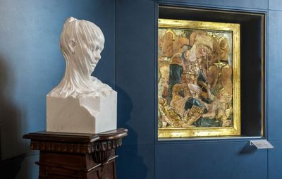 veiled marble bust of a female carved out of a square block, placed on a plinth alongside a Renaissance religious painting