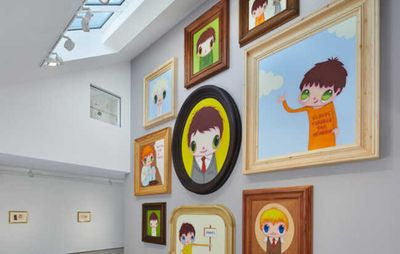 installation view of nine large cartoon portraits stacked around one another on a wall