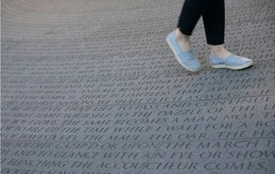 permanent installation of writing engraved into the concrete of a memorial site in New York, as a pair of feet walk over it