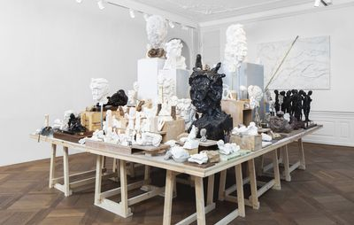 installation view of large table in the centre of a room, with its surface completely covered with sculptures and busts of varying sizes