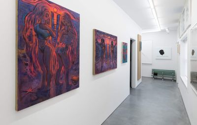 installation view of narrow corridor with paintings hung down it