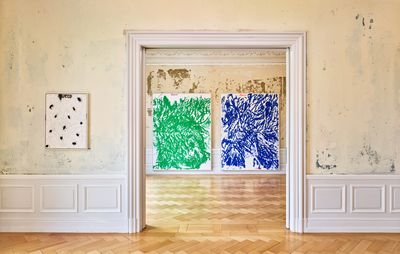 installation view of one painting to the side of a large doorway with two larger abstract paintings visible through the doorway