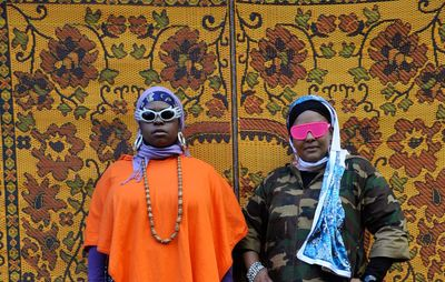 two women in sunglasses with headscarves and long skirts on stood against a yellow tapestry with flowers on it