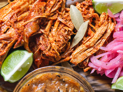 Cochinita pibil, traditional slow-roasted suckling pig, with condiments