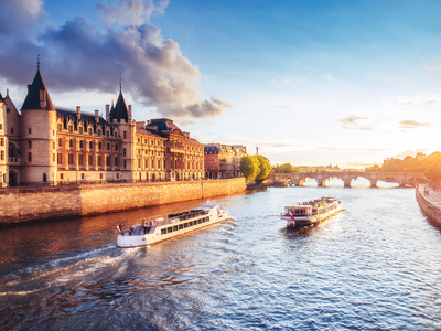 Dramatic sunset over river Seine in Paris, France, with Conciergerie and Pont Neuf.