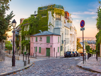 Old street with pink house at sunrise in Montmartre in Paris, France