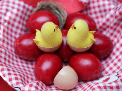 Toy chicks sitting on red eggs