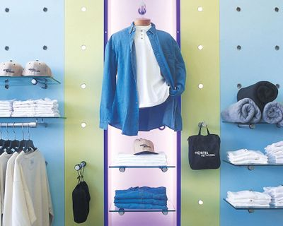Forward shot of a blue, green, and purple wall with holes neatly gridded on it. The holes hold bars which carry shelves displaying clothes and towels.