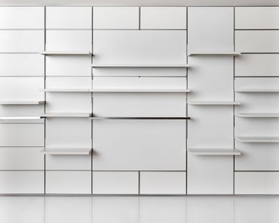 A white wall with lines running across it hold white shelves varying in length.