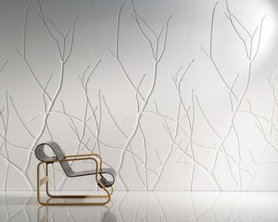 A sleek chair is placed in front of a white wall with branch patterned Iconic Panels.