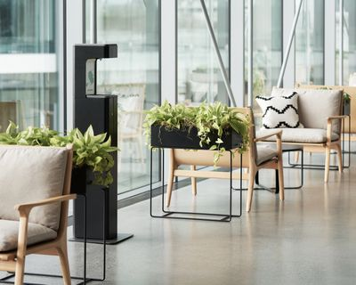 A black Sanitizing Station is placed amongst cushioned chairs and plants lined along the floor.