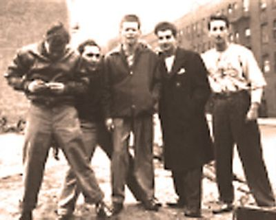 Sepia and aged image of a group of men posing in a street.