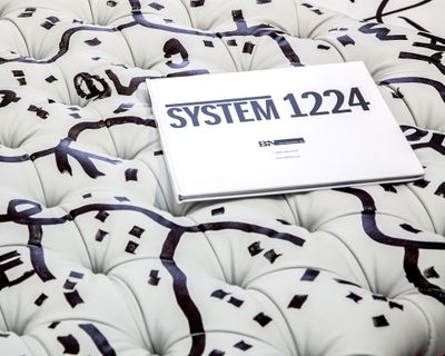 """A white book titled """"System 1224"""" sits on top of a white cushion with line and dotted dark patterns decorating it."""