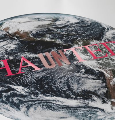 Image of earth with pink text across, Haunted by Cali Thornhill Dewitt - detail shot