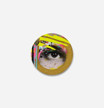 circular print of an eye surrounded by gold glitter and three yellow stripes