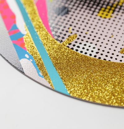 Detail of a corner of a print with gold glitter edge and blue, pink and white stripes