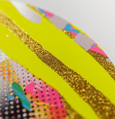 Detail of corner of a print with gold glitter and two yellow stripes over it