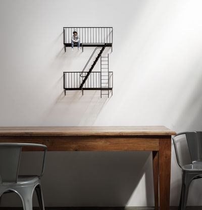 Sculpture of figure sitting on miniature staircase, The Future by Elmgreen & Dragset - in situ