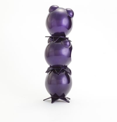 a purple sculpture of three heads in custom helmets stacked on top of each other by Hebru Brantley - back view