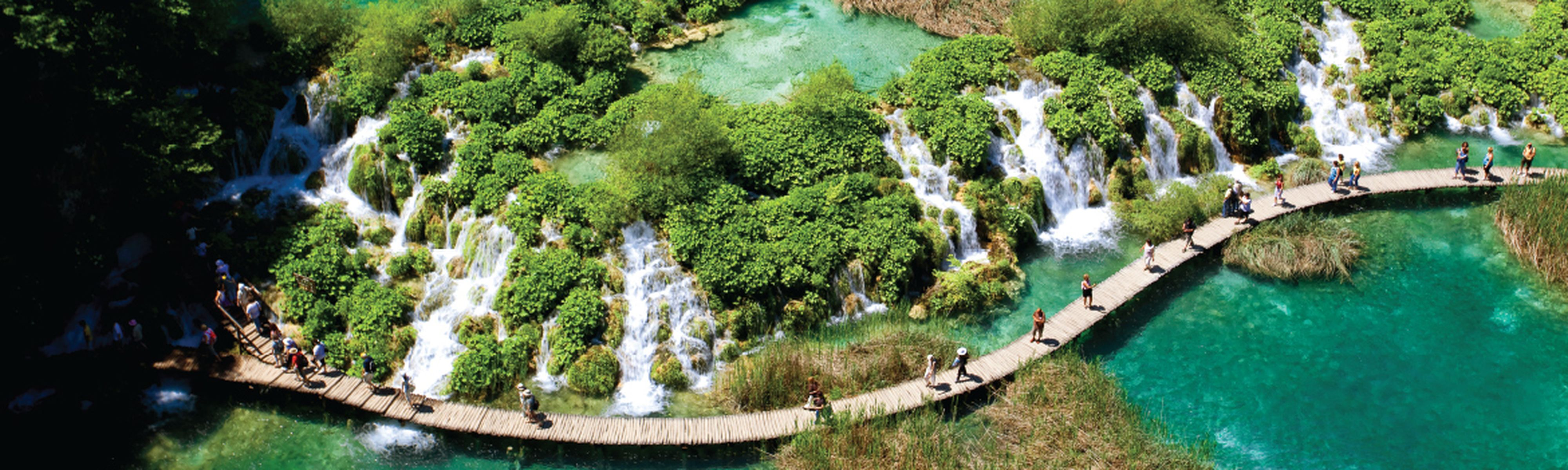 Birdseye view of tourists walking on wooden bridge in Plitvice National Park