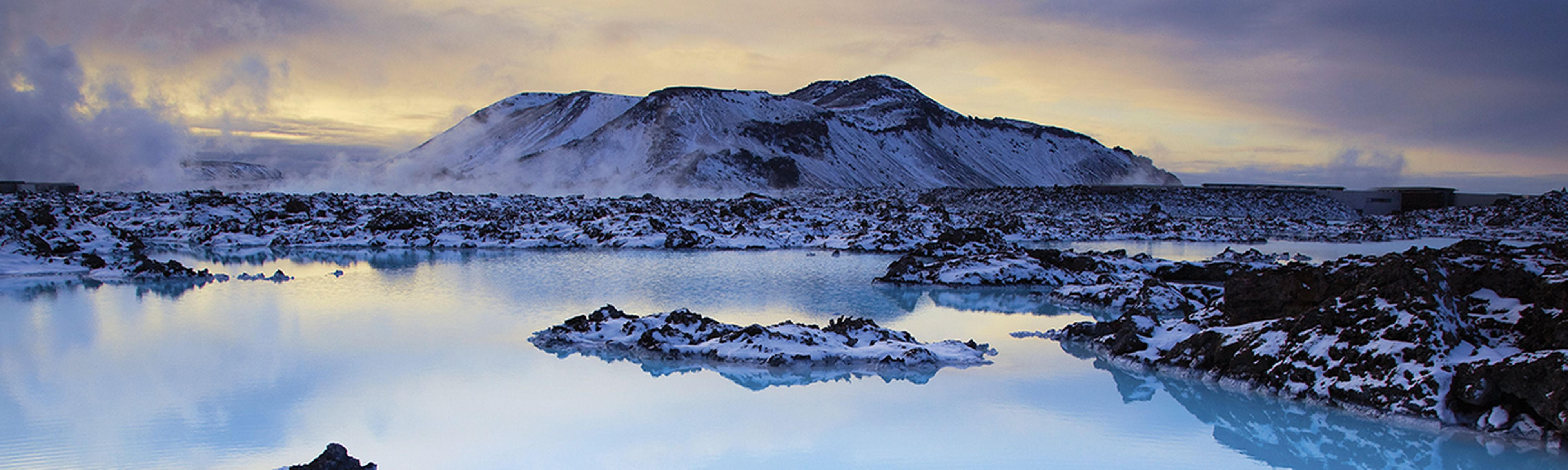 glaciers covered in snow surrounding a lagoon in iceland